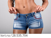 Купить «Woman wearing denim shorts with a beautiful waist. Studio shot», фото № 28535704, снято 10 февраля 2015 г. (c) Ingram Publishing / Фотобанк Лори