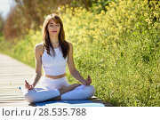 Young woman doing yoga in nature. Female wearing white sport clothes in lotus figure. Стоковое фото, фотограф Javier Sánchez Mingorance / Ingram Publishing / Фотобанк Лори