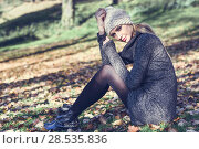 Young blonde woman sitting on full leaves floor in a park with autumn colors. Beautiful girl wearing winter gray dress and wool cap. Female with straight hair and blue eyes. Стоковое фото, фотограф Javier Sánchez Mingorance / Ingram Publishing / Фотобанк Лори