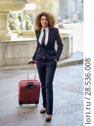 Купить «Beautiful black woman smiling and carrying a rolling suitcase in urban background Businesswoman wearing suit with trousers and tie, afro hairstyle», фото № 28536008, снято 25 ноября 2015 г. (c) Ingram Publishing / Фотобанк Лори