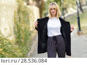 Beautiful blonde woman in urban background. Young girl wearing black blazer jacket and striped trousers standing in the street. Pretty female with straight hair hairstyle and blue eyes. Стоковое фото, фотограф Javier Sánchez Mingorance / Ingram Publishing / Фотобанк Лори