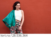 Купить «Young brunette woman, model of fashion, wearing green modern jacket and flower pants on red wall. Pretty caucasian girl with long wavy hairstyle. Female with red lips in urban background.», фото № 28536364, снято 11 марта 2017 г. (c) Ingram Publishing / Фотобанк Лори