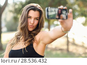 Portrait of a beautiful young woman selfie in the park with a smartphone. Стоковое фото, фотограф Javier Sánchez Mingorance / Ingram Publishing / Фотобанк Лори