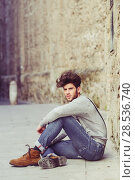 Купить «Portrait of young man wearing suspenders and blue jeans in urban background with modern haircut, sitting on the floor», фото № 28536740, снято 8 апреля 2014 г. (c) Ingram Publishing / Фотобанк Лори