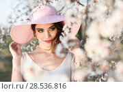 Купить «Portrait of young woman in the flowered field in the spring time. Almond flowers blossoms. Girl wearing white dress and pink sun hat», фото № 28536816, снято 10 марта 2015 г. (c) Ingram Publishing / Фотобанк Лори