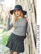 Купить «Beautiful young blonde woman, model of fashion, in rural background. Girl wearing sweater, skirt and hat.», фото № 28536848, снято 17 ноября 2015 г. (c) Ingram Publishing / Фотобанк Лори