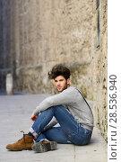 Купить «Portrait of young man wearing suspenders sitting on the floor in urban background», фото № 28536940, снято 8 апреля 2014 г. (c) Ingram Publishing / Фотобанк Лори