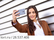 Купить «Young woman taking selfie photograph with smartphone in urban background. Beautiful girl wearing formal wear using smart phone. Young female with brown jacket smiling in urban background.», фото № 28537408, снято 30 апреля 2017 г. (c) Ingram Publishing / Фотобанк Лори