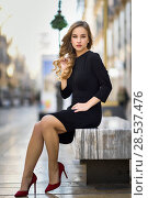 Blonde woman in urban background. Beautiful young girl wearing black elegant dress and red high heels standing in the street. Pretty russian female with long wavy hair hairstyle and blue eyes. Стоковое фото, фотограф Javier Sánchez Mingorance / Ingram Publishing / Фотобанк Лори