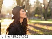 Купить «Portrait of thoughtful woman sitting alone outdoors wearing hat. Nice backlit with sunlight», фото № 28537652, снято 12 января 2016 г. (c) Ingram Publishing / Фотобанк Лори