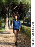 Купить «Young black woman with afro hairstyle walking in urban park. Mixed woman wearing blue shirt and shorts.», фото № 28538248, снято 10 декабря 2016 г. (c) Ingram Publishing / Фотобанк Лори