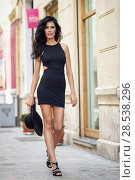 Купить «Brunette woman wearing black seductive dress and sun hat in the street. Young girl with curly hairstyle walking in urban background», фото № 28538296, снято 7 июля 2016 г. (c) Ingram Publishing / Фотобанк Лори