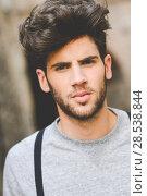 Купить «Portrait of young man wearing suspenders and blue jeans in urban background with modern haircut», фото № 28538844, снято 8 апреля 2014 г. (c) Ingram Publishing / Фотобанк Лори