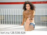 Купить «Portrait of a young black woman, afro hairstyle, wearing beige leather jacket, in urban background», фото № 28538924, снято 11 декабря 2011 г. (c) Ingram Publishing / Фотобанк Лори