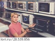 Купить «Positive female looking new microwave for kitchen in furniture store», фото № 28539856, снято 1 марта 2018 г. (c) Яков Филимонов / Фотобанк Лори