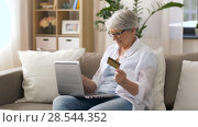 Купить «senior woman with laptop and credit card at home», видеоролик № 28544352, снято 29 мая 2018 г. (c) Syda Productions / Фотобанк Лори