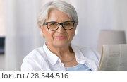 Купить «portrait of senior woman reading newspaper at home», видеоролик № 28544516, снято 29 мая 2018 г. (c) Syda Productions / Фотобанк Лори