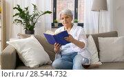 Купить «senior woman reading book at home», видеоролик № 28544732, снято 29 мая 2018 г. (c) Syda Productions / Фотобанк Лори