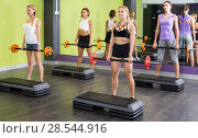 Купить «Portrait of sporty women exercising with barbell in fitness club», фото № 28544916, снято 26 июля 2017 г. (c) Яков Филимонов / Фотобанк Лори