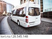 Купить «White mini bus moves down the street», фото № 28545148, снято 2 августа 2017 г. (c) Юрий Бизгаймер / Фотобанк Лори