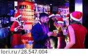 Купить «Young cheerful people with cocktails in Santa hats celebrating at nightclub», видеоролик № 28547004, снято 21 декабря 2017 г. (c) Яков Филимонов / Фотобанк Лори