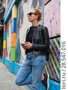 Купить «Woman using smartphone against colorful graffiti wall in New York city, USA.», фото № 28547016, снято 4 апреля 2020 г. (c) Matej Kastelic / Фотобанк Лори