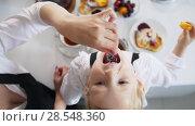 Купить «Top view of mom and her little girl drinks tea and eats cherry», видеоролик № 28548360, снято 27 мая 2020 г. (c) Константин Шишкин / Фотобанк Лори
