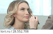 Applying blush makeup with brush to cheekbones of smiling young woman. Стоковое фото, фотограф Vasily Alexandrovich Gronskiy / Фотобанк Лори