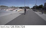 Купить «Electric Longboard man in sweatshirt and hat ride on red sport stadium with playground», видеоролик № 28554724, снято 9 июня 2018 г. (c) Aleksejs Bergmanis / Фотобанк Лори