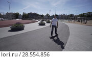 Купить «Electric Longboard man in white t-shirt and hat ride on red sport stadium with playground», видеоролик № 28554856, снято 9 июня 2018 г. (c) Aleksejs Bergmanis / Фотобанк Лори
