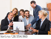 Купить «colleagues looking at laptop and smiling», фото № 28554960, снято 20 февраля 2019 г. (c) Яков Филимонов / Фотобанк Лори