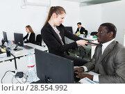 Купить «Businesswoman flirting with African American male in office», фото № 28554992, снято 24 марта 2018 г. (c) Яков Филимонов / Фотобанк Лори