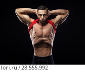 Купить «Cute young sports man in red t-shirt shows relief and vacuum abdominal muscles», фото № 28555992, снято 16 марта 2018 г. (c) Restyler Viacheslav / Фотобанк Лори