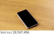 Купить «smartphone with blank black screen on wooden table», видеоролик № 28567496, снято 20 октября 2019 г. (c) Syda Productions / Фотобанк Лори