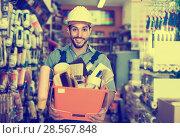 Купить «Smiling man builder with tools in hands in shop», фото № 28567848, снято 13 сентября 2017 г. (c) Яков Филимонов / Фотобанк Лори