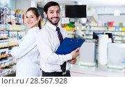 Купить «Two pharmacists standing in drugstore», фото № 28567928, снято 28 февраля 2018 г. (c) Яков Филимонов / Фотобанк Лори