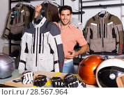 Купить «Man is demonstrating new jacket for motorbike in the store.», фото № 28567964, снято 1 сентября 2017 г. (c) Яков Филимонов / Фотобанк Лори