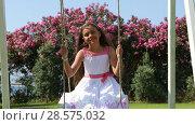 Купить «Adorable little girl in white dress swinging on a swing in the city park», видеоролик № 28575032, снято 12 июня 2018 г. (c) Алексей Кузнецов / Фотобанк Лори