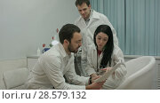 Купить «Two physicians in good mood analyze results of patient to diagnose disease, then comes intern with x-ray», видеоролик № 28579132, снято 24 ноября 2015 г. (c) Vasily Alexandrovich Gronskiy / Фотобанк Лори