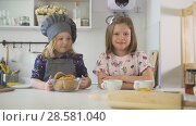 Купить «Two little sisters smiling with homemade cookies and cups of tea at cooking studio», фото № 28581040, снято 22 июля 2018 г. (c) Константин Шишкин / Фотобанк Лори
