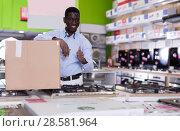 Купить «Male with box of purchases in household appliances store», фото № 28581964, снято 21 февраля 2018 г. (c) Яков Филимонов / Фотобанк Лори