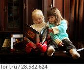 Купить «Две маленькие девочки читают книгу», фото № 28582624, снято 7 декабря 2019 г. (c) Марина Володько / Фотобанк Лори