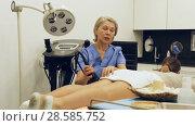 Купить «Professional cosmetician explaining future hardware procedure to female patient», видеоролик № 28585752, снято 28 апреля 2018 г. (c) Яков Филимонов / Фотобанк Лори