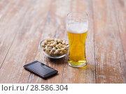 Купить «glass of beer, smartphone and pistachio on table», фото № 28586304, снято 24 ноября 2017 г. (c) Syda Productions / Фотобанк Лори