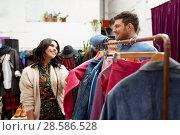 Купить «happy couple at vintage clothing store hanger», фото № 28586528, снято 30 ноября 2017 г. (c) Syda Productions / Фотобанк Лори
