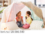 Купить «little girls with torch light in kids tent at home», фото № 28586540, снято 18 февраля 2018 г. (c) Syda Productions / Фотобанк Лори