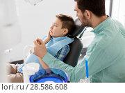 Купить «father supporting son at dental clinic», фото № 28586608, снято 22 апреля 2018 г. (c) Syda Productions / Фотобанк Лори