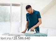 Купить «man ironing shirt by iron at home», фото № 28586640, снято 10 мая 2018 г. (c) Syda Productions / Фотобанк Лори