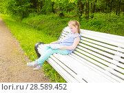Купить «Girl sits on a settle and reads a interesting book», фото № 28589452, снято 11 июня 2017 г. (c) Сергей Дубров / Фотобанк Лори