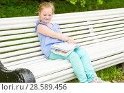 Купить «Schoolgirl is reading a book and dreaming», фото № 28589456, снято 11 июня 2017 г. (c) Сергей Дубров / Фотобанк Лори